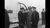 Two shots of Harry Hopkins special emissary for US President Franklin Roosevelt leaving ship accompanied by man / military officers talking on deck...