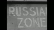 Two shots of line of people running across border between East and West Germany / CU sign that reads 'Russian Zone' / crowd of people at night...