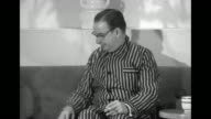 / two shots of man sitting on couch modeling pajamas at Bonwit Teller department store he smokes a cigarette / same man standing with woman who wears...