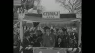Two shots of man standing on outdoor platform and giving speech in English with Polish and Polish American officials behind him during the city's...