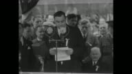 Two shots of PolishAmerican M S Szymczak Chicago City Comptroller standing on platform with Polish officials and giving speech in Polish and then...