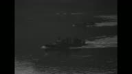 Two shots of searchlights at night / US soldiers looking across Rhine River at night / searchlight shining on water / VS amphibious vehicles crossing...