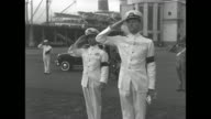 Two shots of stern of ship USS Mount Olympus and gangplank coming down for it and US flag waving at half mast on ship / two Navy officers standing on...