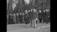 Two shots of US soldiers standing in formation presenting arms / Luxembourg Minister of Foreign Affairs Joseph Bech standing in front of dedication...