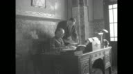 Two shots of Vichy French Gen Maxime Weygand Governor General of Algeria sitting in office at desk while man standing next to him hands him documents...