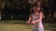 SLO MO MS Two sisters running and chasing bubbles in yard / Los Angeles, California, USA
