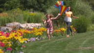 WS Two sisters (12-13, 16-17) running with kites in park / Utah, USA