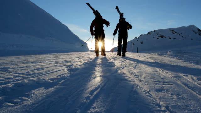 Two skiers walking towards the falling sun