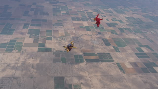 Two skydivers exit plane in a rodeo dive, with one riding on top of the other's back.  Another skydiver flies around them.