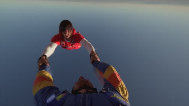 Two skydivers holding hands and spinning through the sky, then one skydiver deploys his parachute.