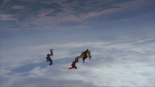 Two skydivers perform a rodeo dive with one on top of the others back.  Another skydiver and camera flyer fly around them.