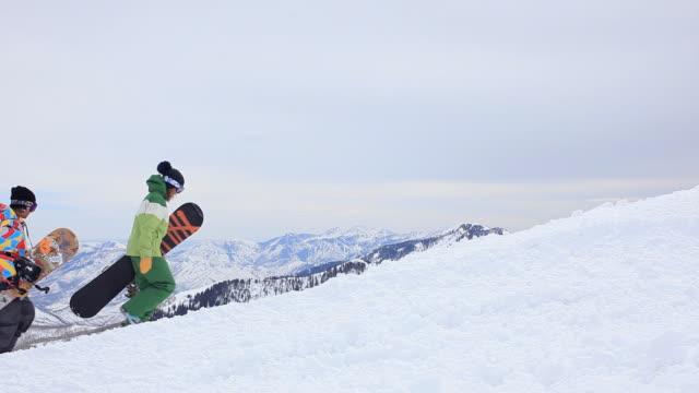 WS Two snowboarders walking on snow at ski resort / Brighton Ski Resort, Utah, USA