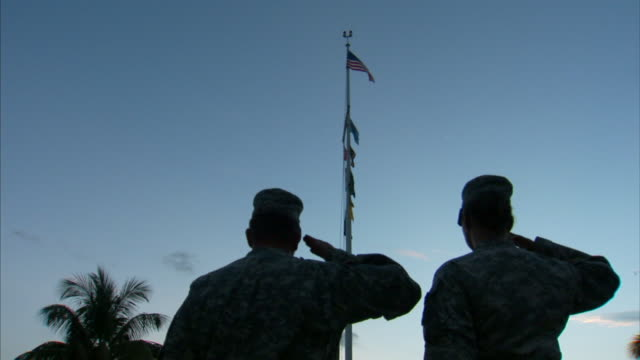 Two Soldiers in camouflage uniforms standing facing Marine flagpole with American flag and nautical flags on pole soldiers saluting SOT Bugle playing...