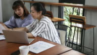 two southeast asia woman talking and working in cafe