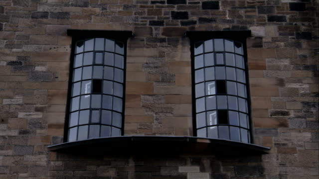 Two tall windows framed in iron adorn the facade of the Glasgow School of Art, Scotland. Available in HD.