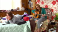 WS DS Two teen girls playing acoustic guitar and watching tv in bedroom / Brooklyn, New York, USA