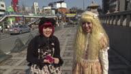 MS Two teen girls wearing costumes on street, Tokyo, Japan