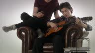 Two teenage boys playing the guitar.
