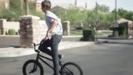 Two teenage boys riding their BMX bikes through the suburbs