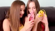 Due ragazze adolescenti che si diverte con i telefoni fissi ed i cellulari