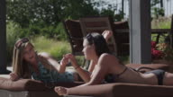 MS Two teenage (16-17) girls in bikini lying on sunloungers and listening music, American Fork, Utah, USA