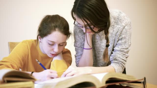 Two teenager girls doing writing homework together