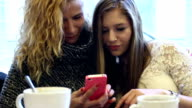 Two teenager girls looking pictures on a cell phone