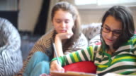 Two teenager girls, sisters, writs something in the notepad