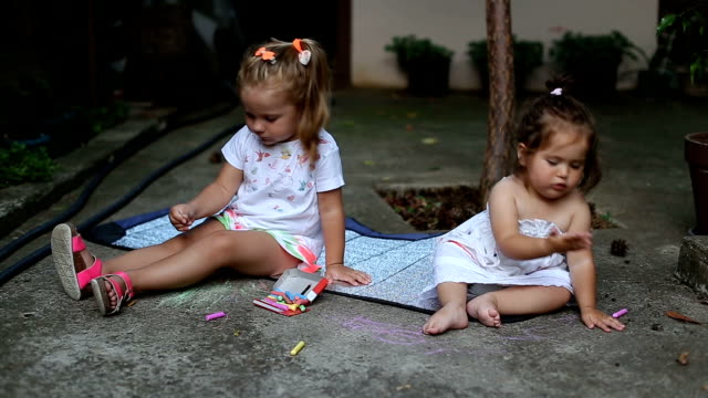 Two toddlers drawing outside with color chalks