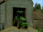 Two tractors leave barn on farm