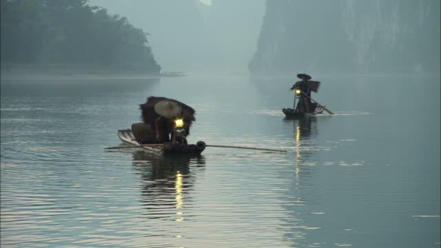 MS, two traditional cormorant fishermen on Li River at dusk, Guangxi province, China