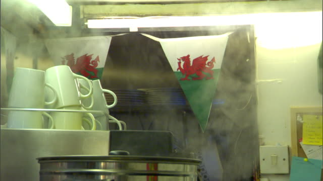 HD HANDHELD Two triangular Flag of Wales hanging from rope over possibly a coffee machine steam rising from machine Welsh UK pride proud patriotic