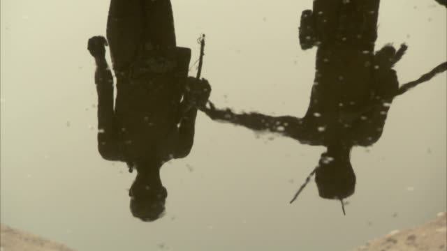 Two tribesmen reflected in the surface of a water tank. Available in HD