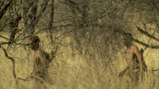 Two tribesmen run through the bush. Available in HD