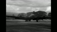 Two US bombers flying low overhead / bomber lands on airfield and taxis past camera / bomber flying low overhead / fighter plane taking off /...