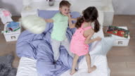 two very cute little kids (brother and sister) having great fun in bedroom - pillow fight