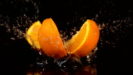 Two videos of falling quarter of orange in real slow motion