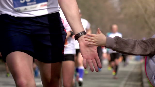 Two videos of giving runners high five -real slow motion