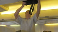Two videos of man putting luggage to overhead cabin-4K