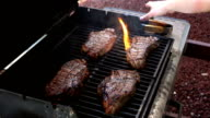 Two videos of opening the grill with steaks-real slow motion