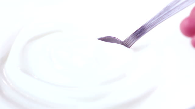Two videos of scooping yogurt in real slow motion
