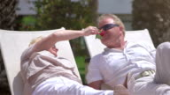 Two videos of senior couple flirting on the sunbeds-slow motion