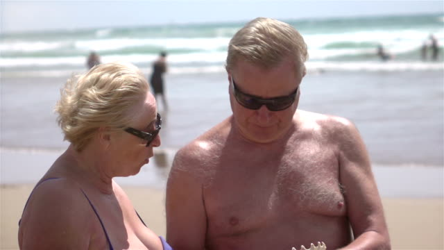 Two videos of senior couple holding shell -slow motion