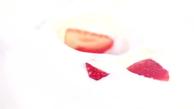 Two videos of strawberries falling into yogurt in real slow motion