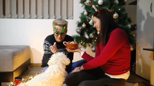 Two woman and dog enjoying in cuddling in Christmas time