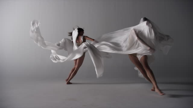 two woman draped with silk running elegantly around in circle in front of camera