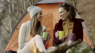 Two woman sitting by campfire