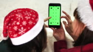 Two woman using Smart phone with Greens screen For Christmas