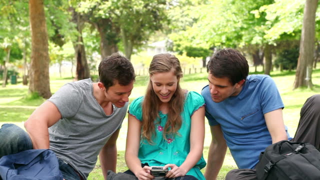 Three friends posing as they take a photo of themselves before laughing