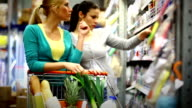 Two women buying cosmetics in supermarket.